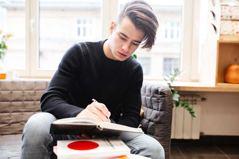 Fiú ülve ír egy könyvbe