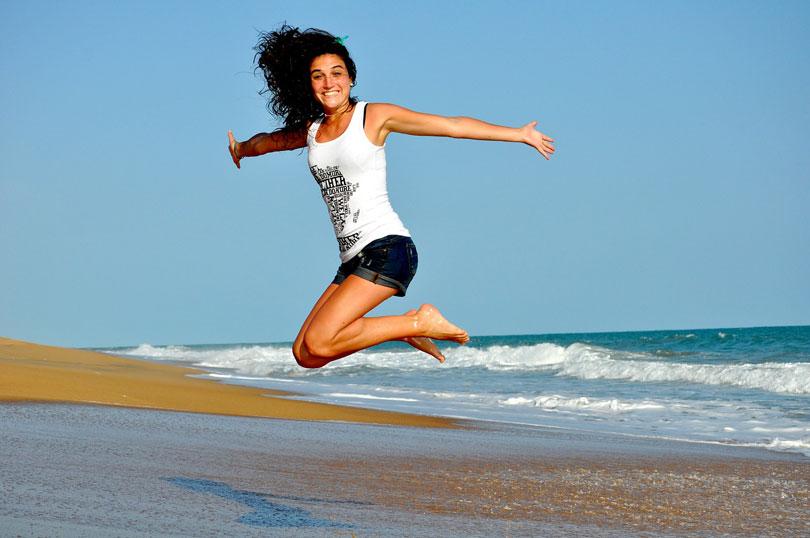 Egy tengerparton felugró boldog, mosolygós nő
