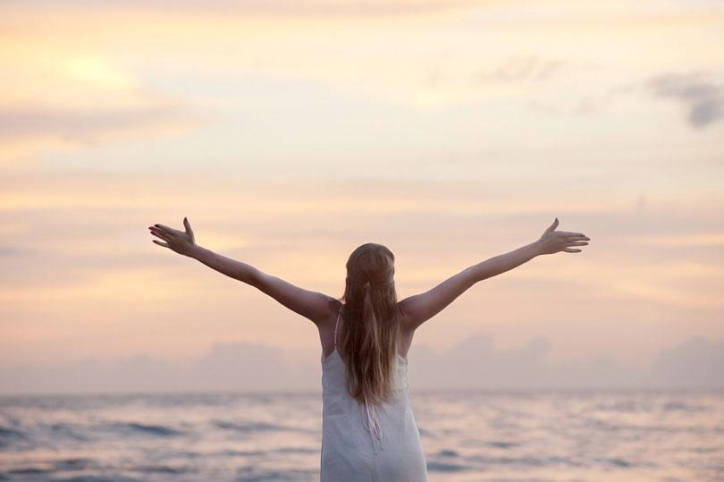 Nő a tengerparton kitárt karral