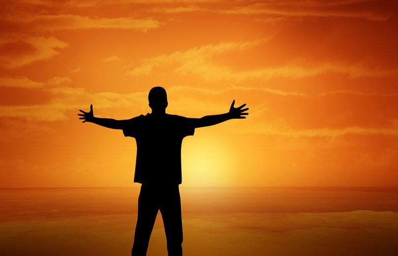 Egy férfi tengerparton naplemente közben széttárt kézzel