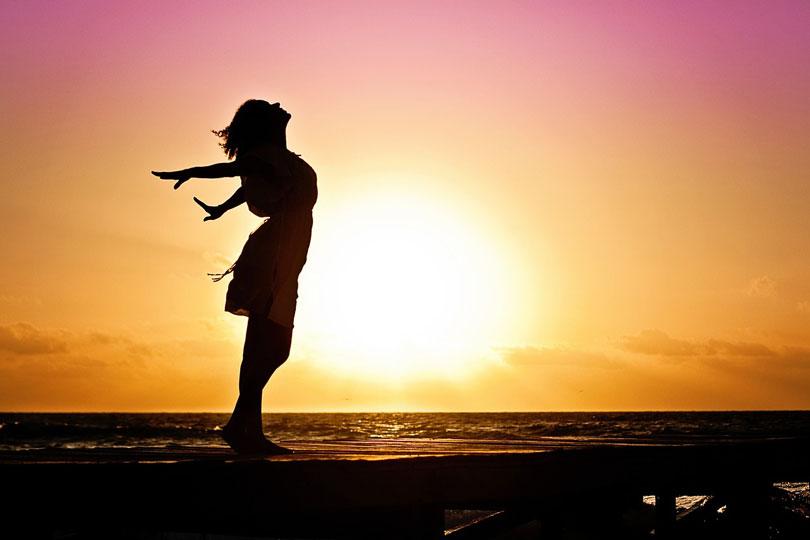 Nő a tengerparton naplementében széttárt karral