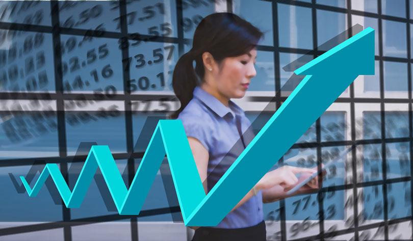 Nő tableten dolgozik előtte egy emelkedő értékeket mutató grafikon-önbizalom növelés