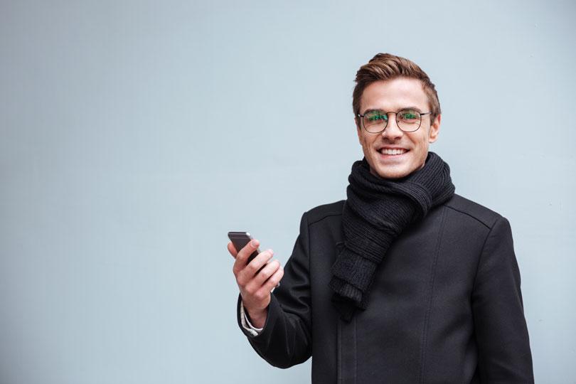 Egy szemüveges férfi kezében egy okos telefonnal - személyes hatékonyság