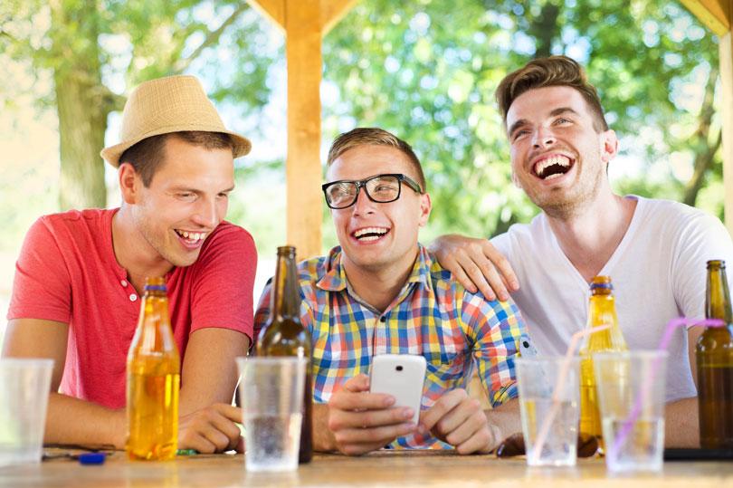 Három férfi sörözés közben nevetve a mobiltelefont nézik