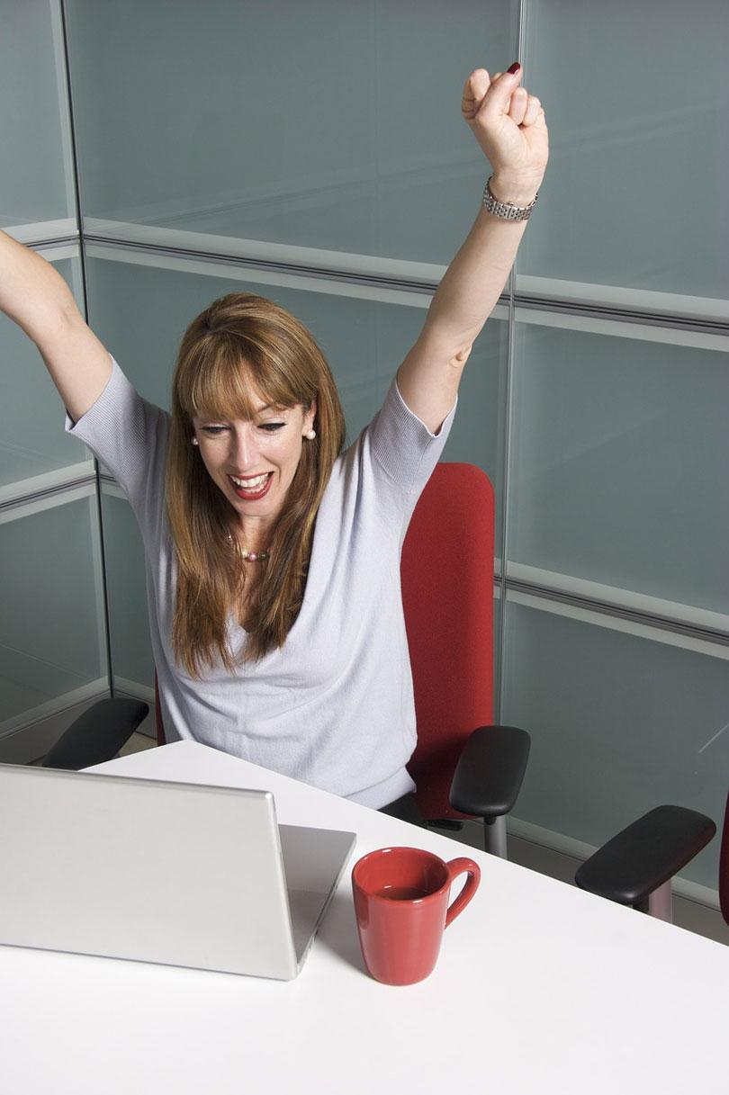 Egy nő az asztalnál felemelt kézzel, boldog felkiáltással - állás megtartása