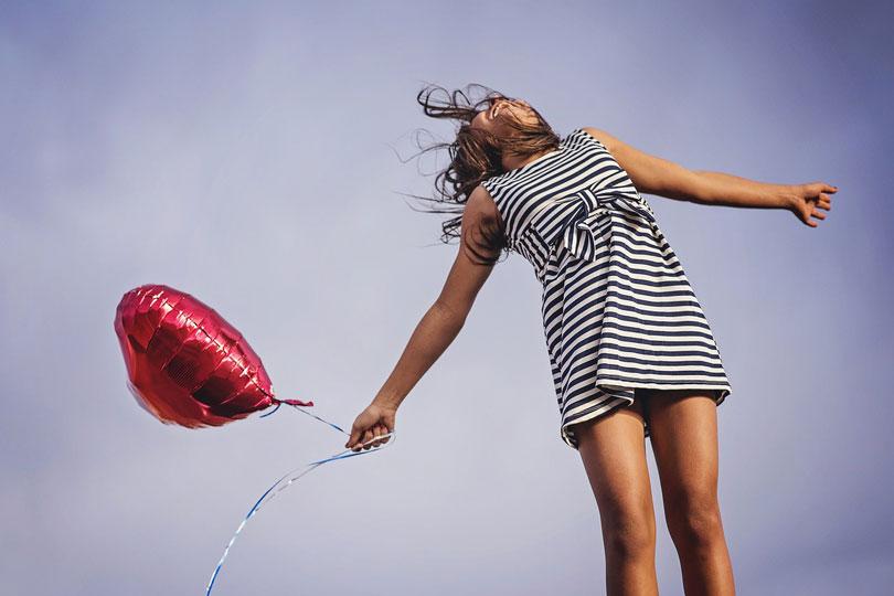 Egy csíkos ruhás nő nevetve tart egy piros lufit - állás megtartása