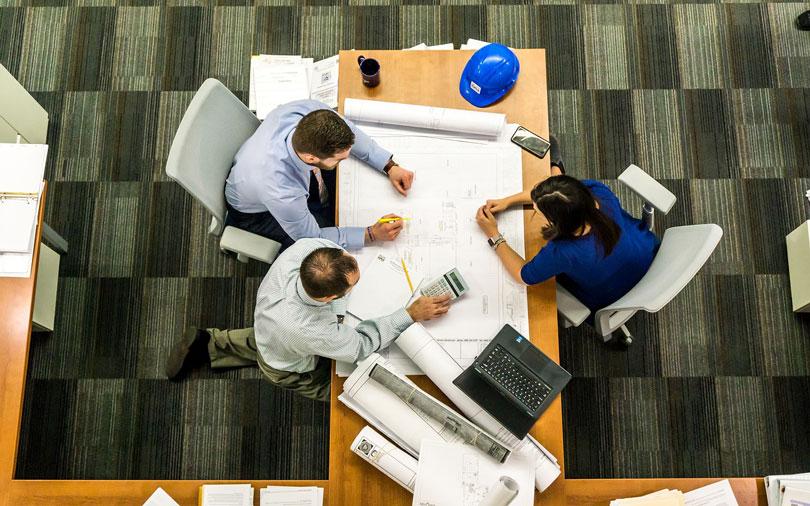 Egy asztal mellett dolgozó két férfi és nő felül nézetből - állás megtartása