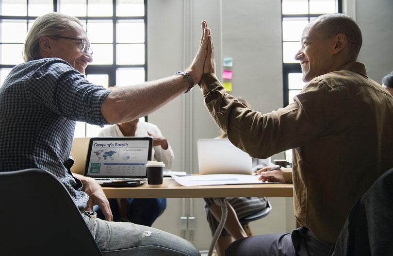 két férfi egy asztal mellett mosolyogva össze ütik a tenyerüket - állás megtartása