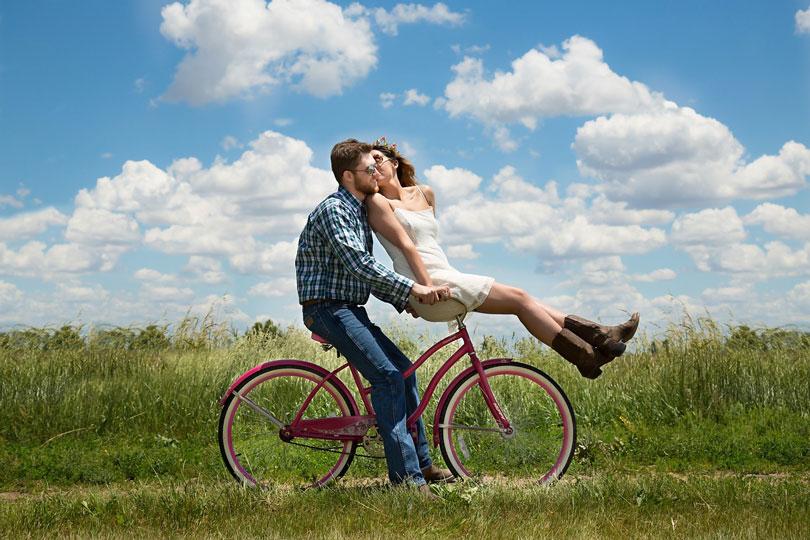 Biciklin ülő férfi és a kormányon ülő nő puszit ad neki - párkapcsolat