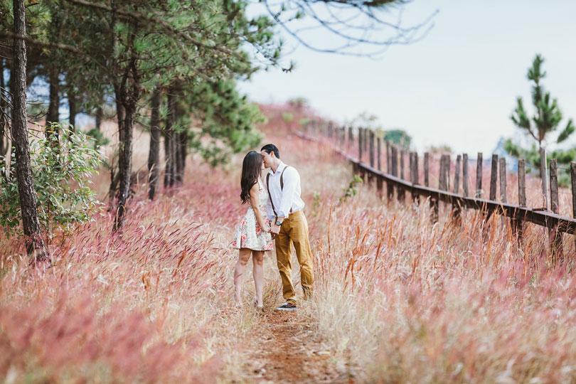 Férfi és nő csókolóznak egy réten kézen fogva - párkapcsolat