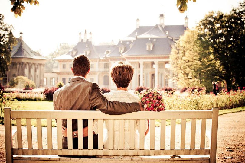 Férfi és nő elegáns ruhában ülnek egy padon átkarolva egymást - párkapcsolat