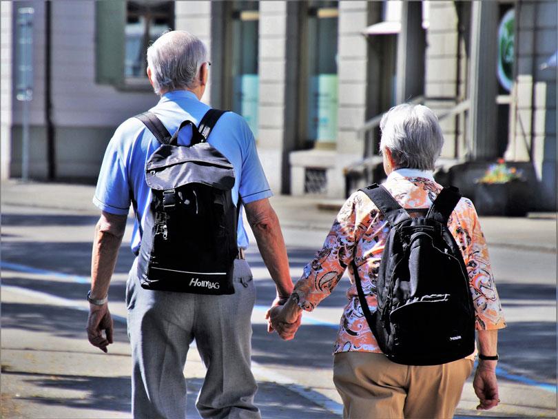Idős férfi és idős nő kézen fogva sétálnak - párkapcsolat