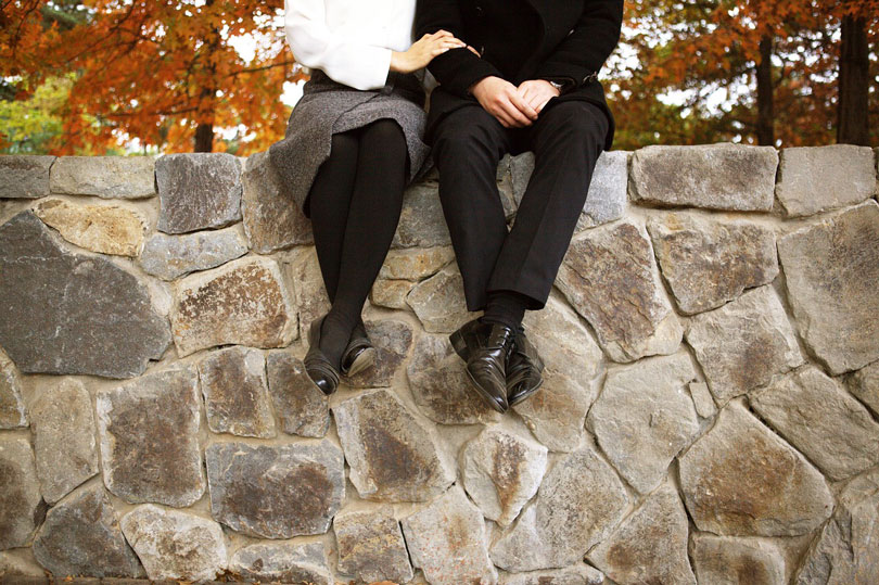 Férfi és nő ülnek egy kő kerítésen - parkapcsolat