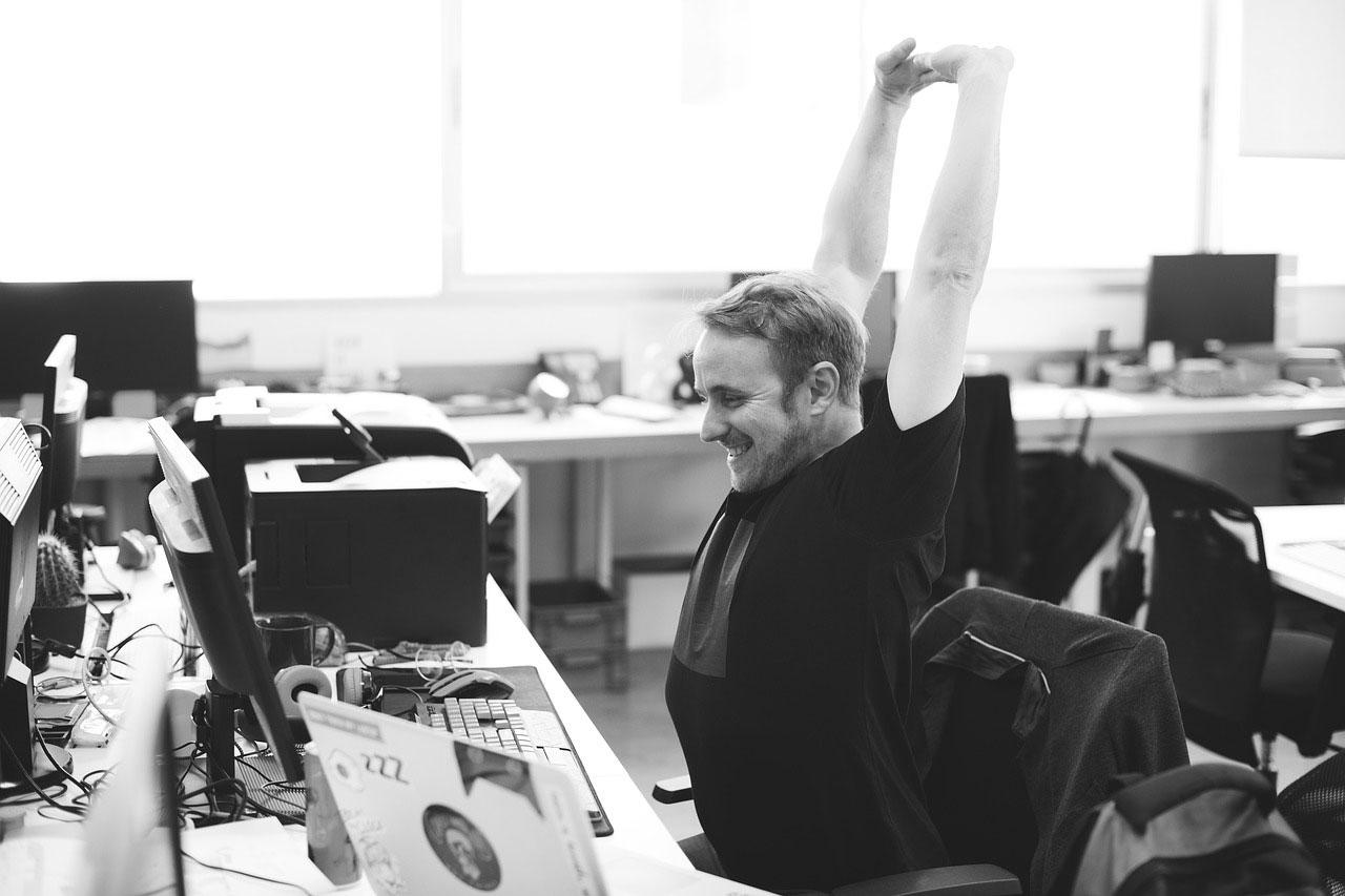 Egy férfi egy irodai munkahelyen elégedetten nyújtózkodik. - Munka