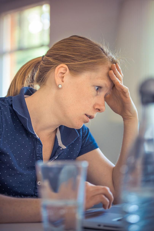 Egy nő fogja a fejét munka közben